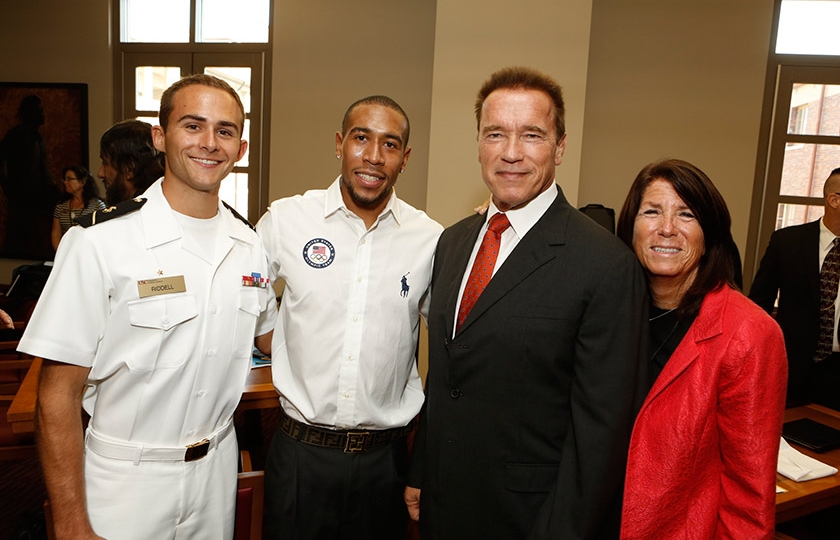 NROTC Midshipman Greg Riddell, Olympic medalist Bryshon Nellum, Governor Arnold Schwarzenegger, and Institute Global Director Bonnie Reiss celebrate the launch of the institute
